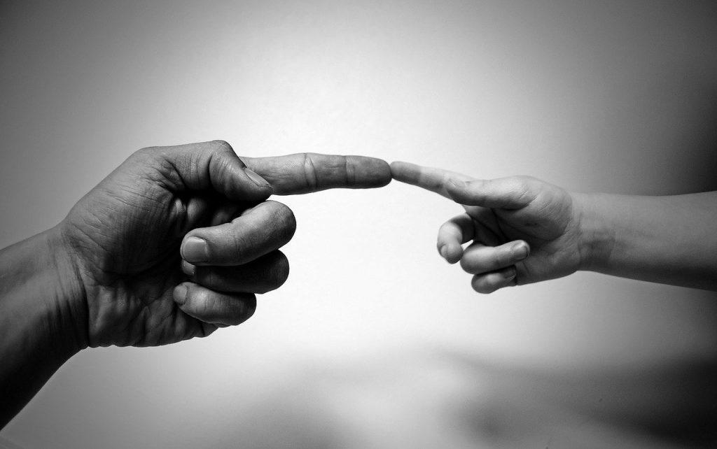 doua persoane se ating cu un deget pe un fundat alb negru