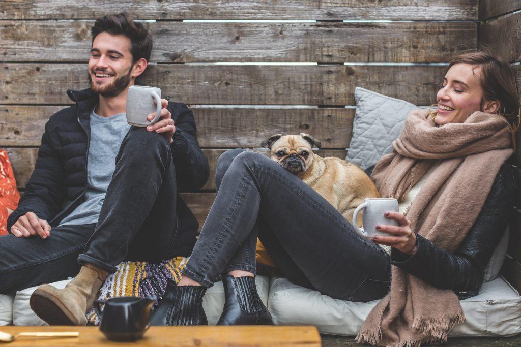 cuplu ce servest o ceasca de ceai la o cabana impreuna cu un caine